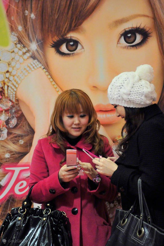 Amigas passam fotografias-Purikura, Shibuya, Tóquio, Japão