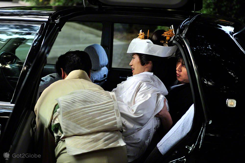 Noiva é encaixada em carro-casamento tradicional, templo Meiji, Tóquio, Japão
