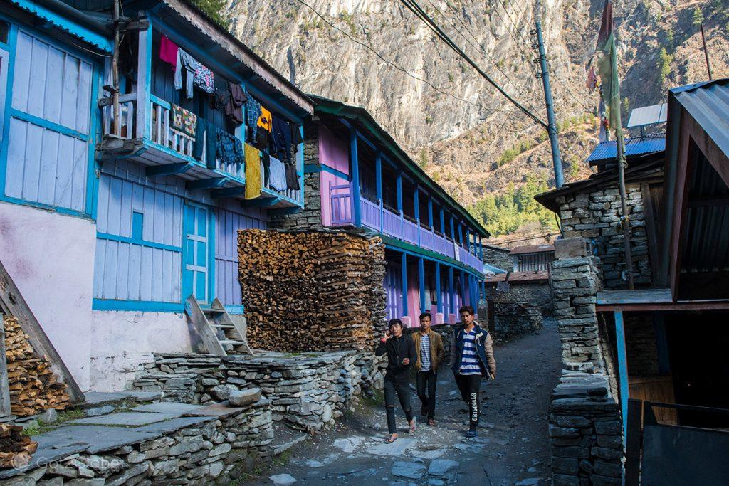 Jovens percorrem a rua principal de Chame, Nepal