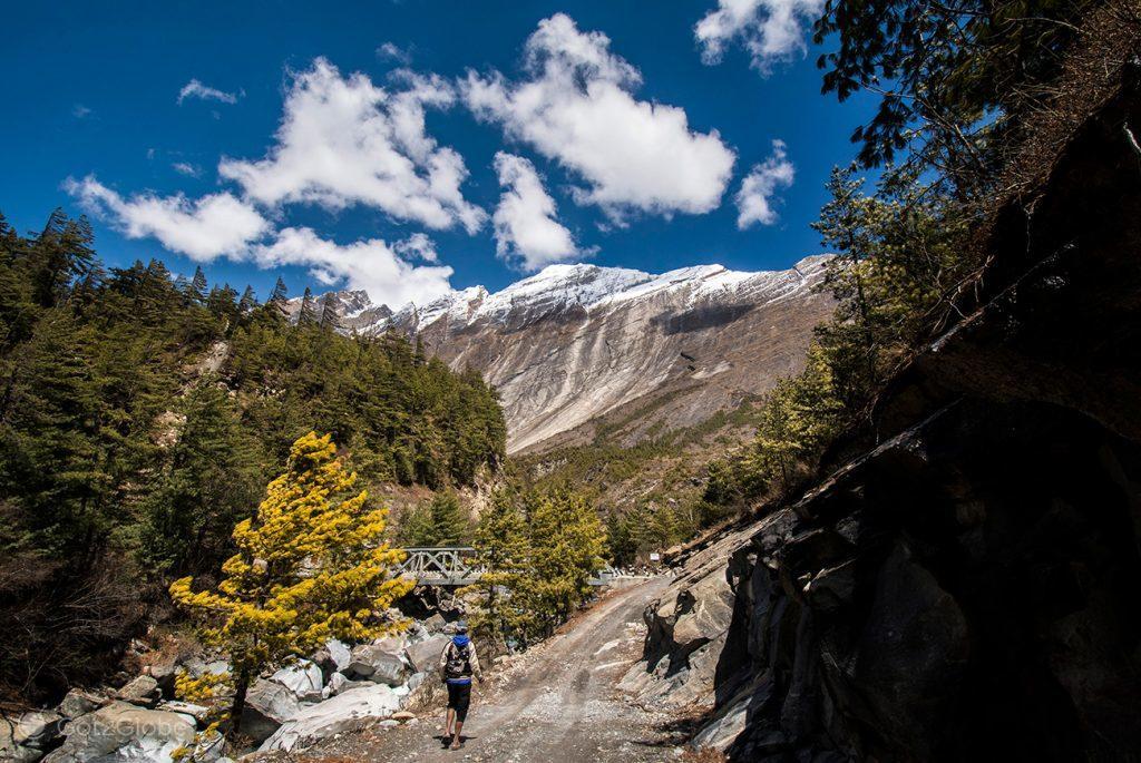 Caminhante à beira do rio Marsyangdi, Circuito Annapurna, Nepal