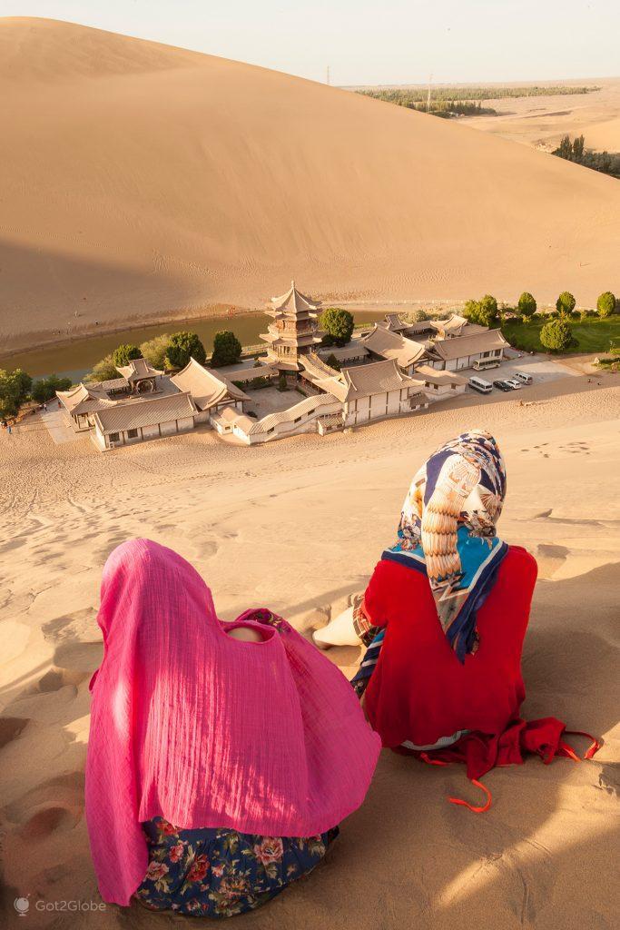 Turistas chinesas apreciam o Lago Crescente, Dunhuang, China