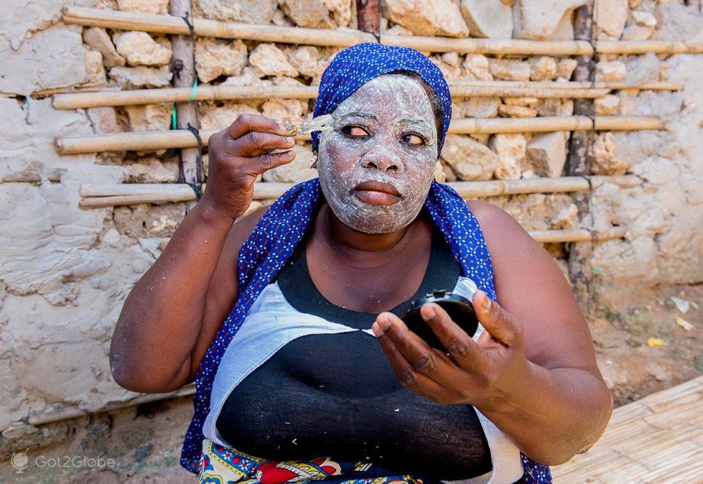 Moradora da ilha de Moçambique compõe máscara de mussiro, Moçambique
