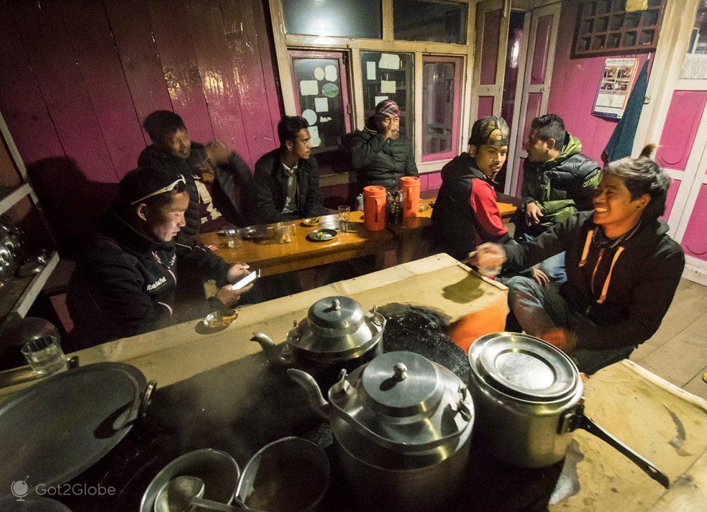 Guias, condutores e carregadores na cozinha do Himalyan Hotel, em Chame, Nepal