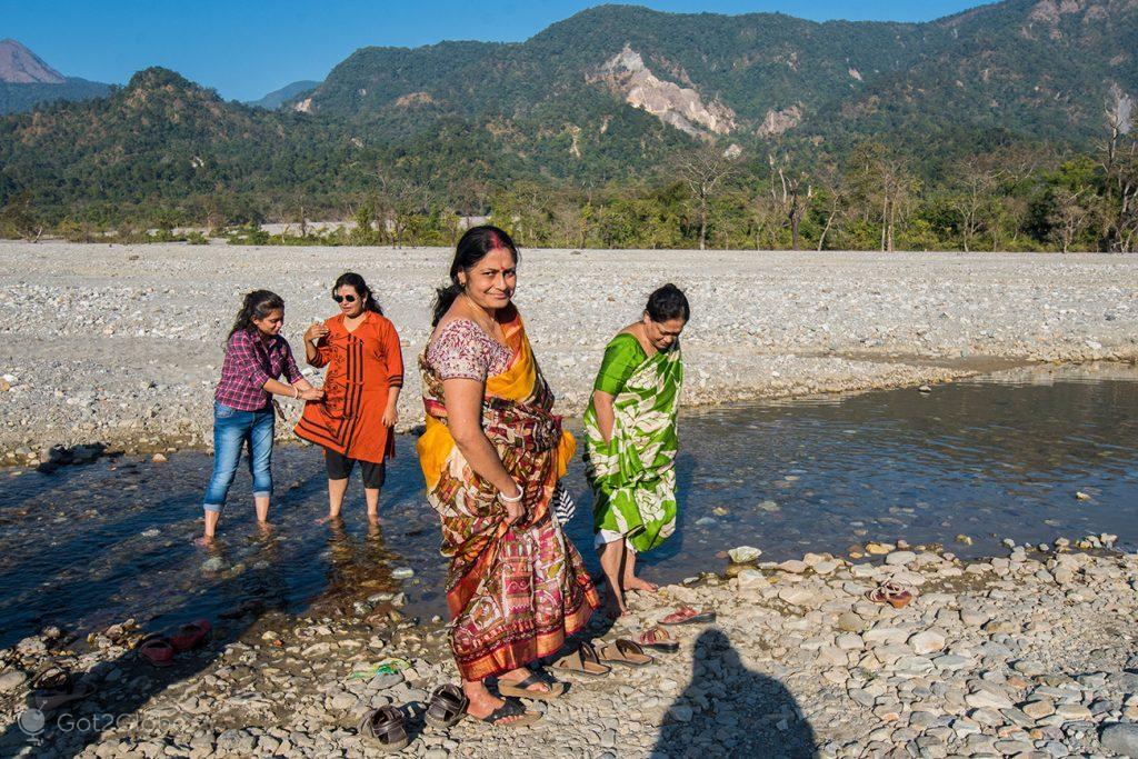 Senhoras indianas cruzam um riacho do rio Jayanti, Bengala Ocidental, Índia