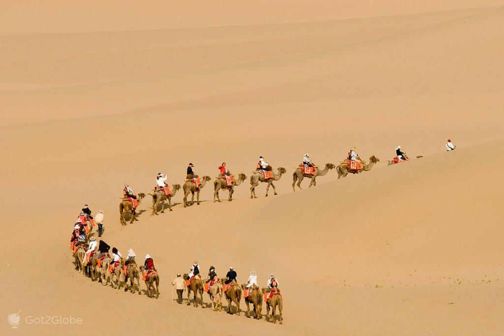 Caravana de visitantes na duna de Minghsan, Dunhuang, China