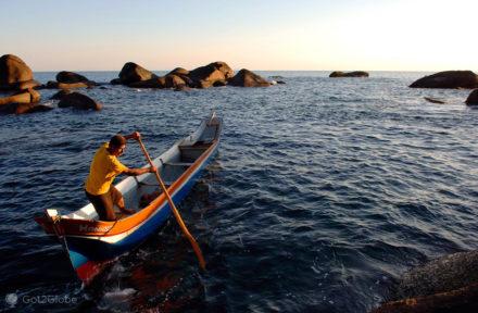 Pescador manobra barco junto à Praia de Bonete, Ilhabela, Brasil