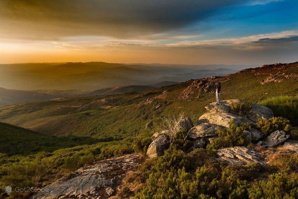 Visitante admira o pôr-do-sol na serrania acima de Castro Laboreiro, Gerês, Portugal