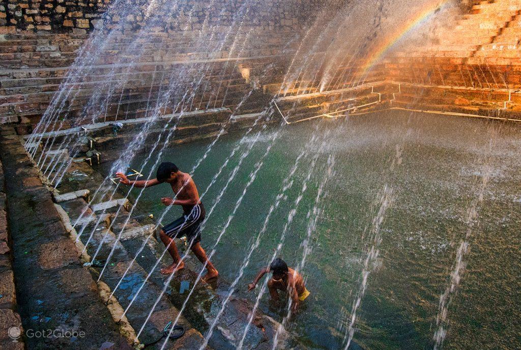 Rapazes a banhar-se na piscina da bendição do templo de Kamakhya, estado de Assam, Índia