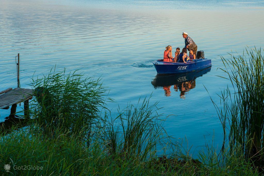 Barqueiro e passageiros no Lago Nero, Rostov Veliky, Rússia