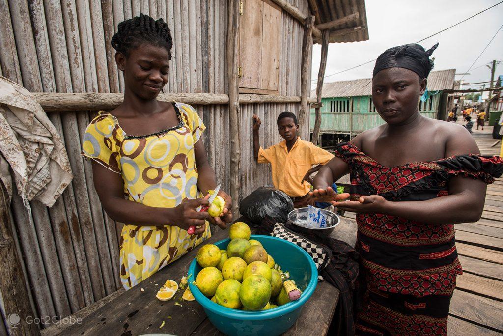 Vendedora de citrinos em Nzulezu, Gana