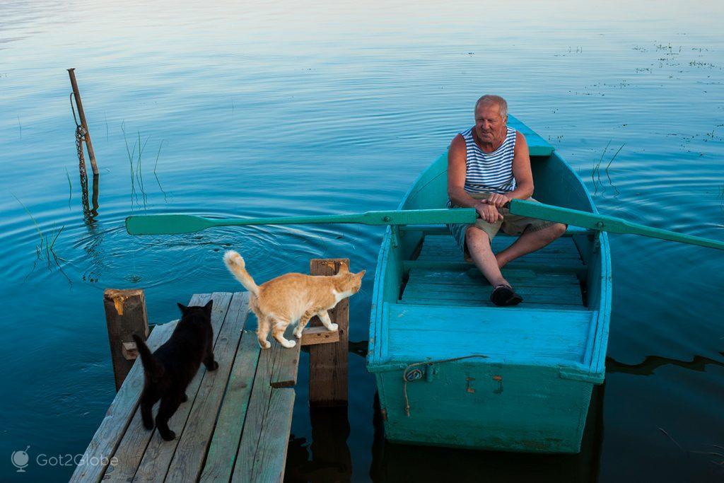 Barqueiro e gatos, no lago Nero, Rostov Veliky, Rússia