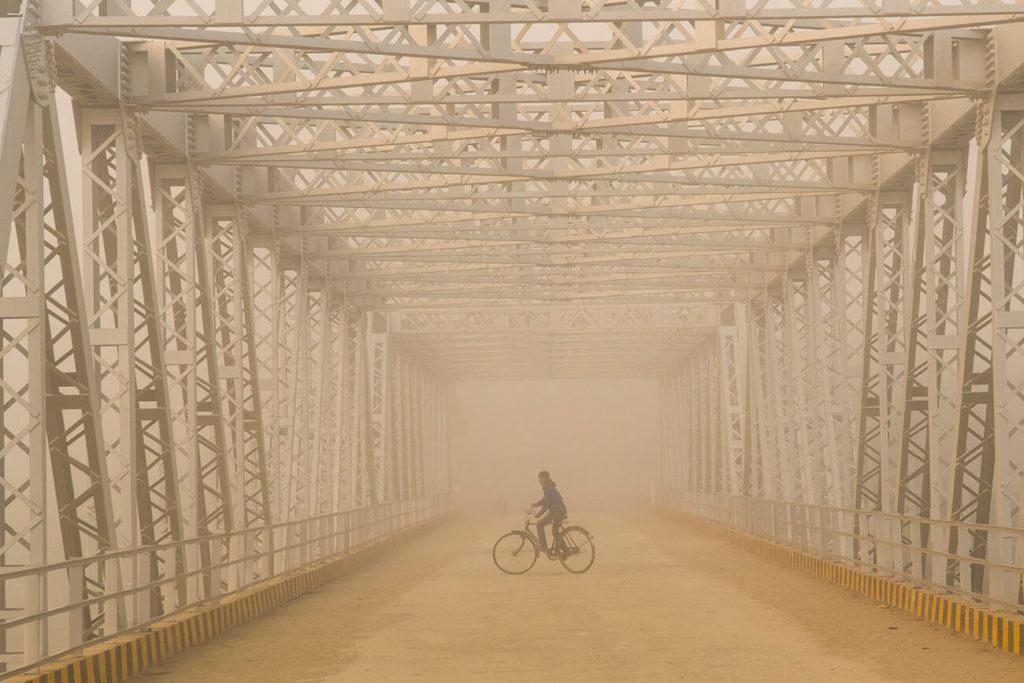 Ciclista na ponte sobre o rio Doom-Domla, Maguri Beel, Assam, Índia