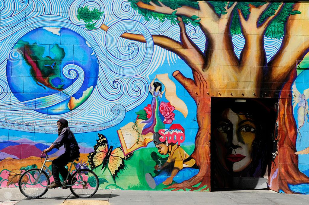 Ciclista paCiclista passa por mural excêntrico de São Francisco, Califórnia, Estados Unidos da América