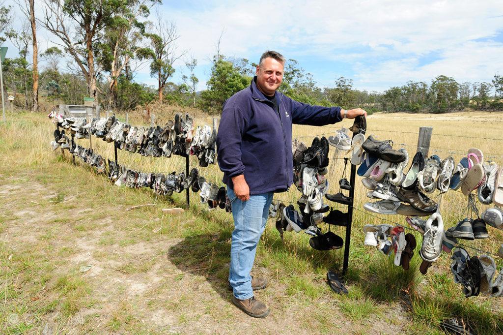 Condutor junto a estendal de calçado velho na beira da estrada, Tasmânia, Austrália