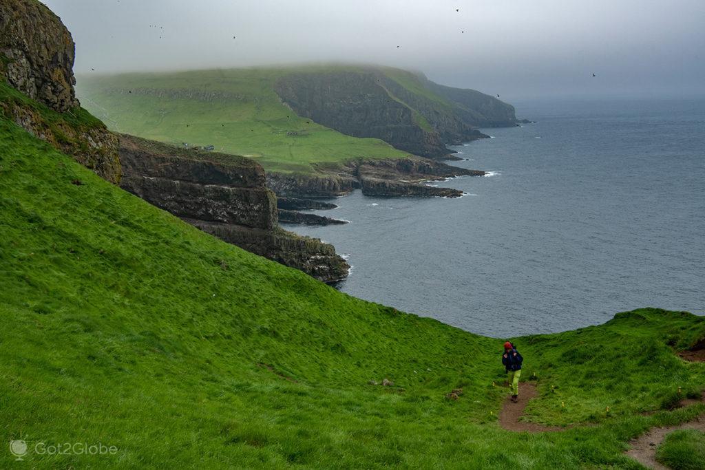 Caminhante num trilho de Mykinesholmur, Mykines, Ilhas Faroé