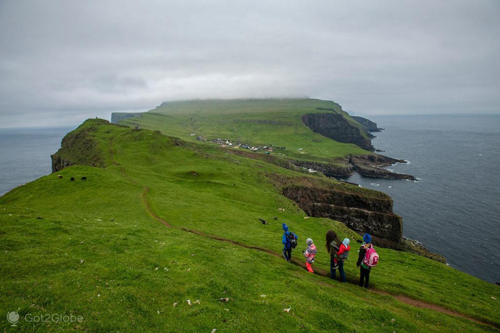 Jovens visitantes regressam à povoação de Mykines, Ilhas Faroé