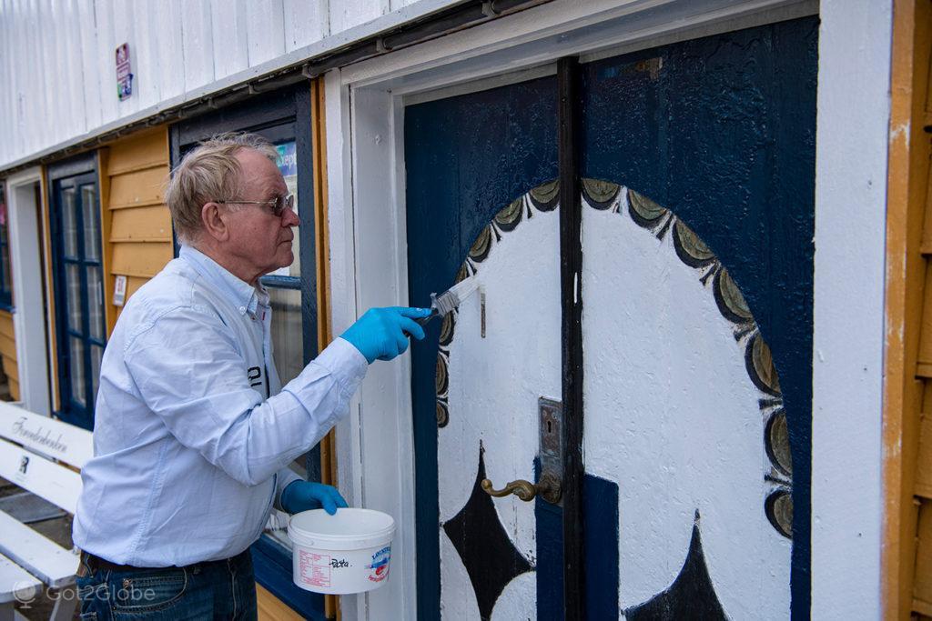 Morador pinta uma porta tradicional, Sokndalstrand, Rogaland, Noruega