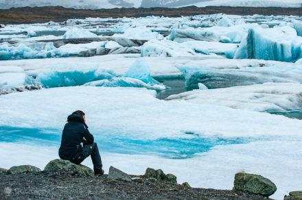 Viajante acima da lagoa gelada de Jökursarlón, Islândia