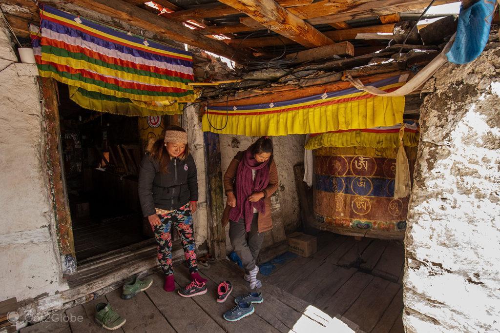 Fiéis tiram calçado, gompa de Milarepa, Circuito Annapurna, Nepal